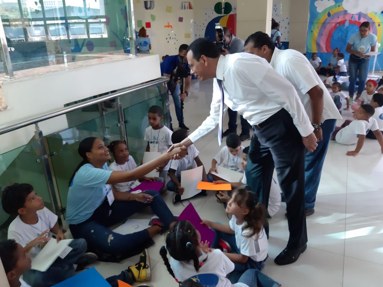 Imagen Ministro de Educación saluda a facilitadora sentada en el piso junto a grupo de niños.