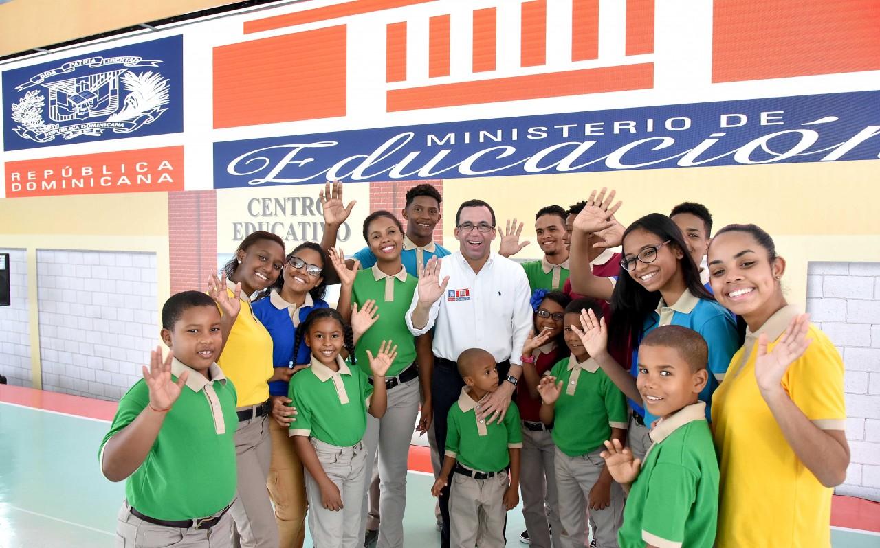 imagen Ministro Andres Navarro junto a estudiantes saludando de pie.