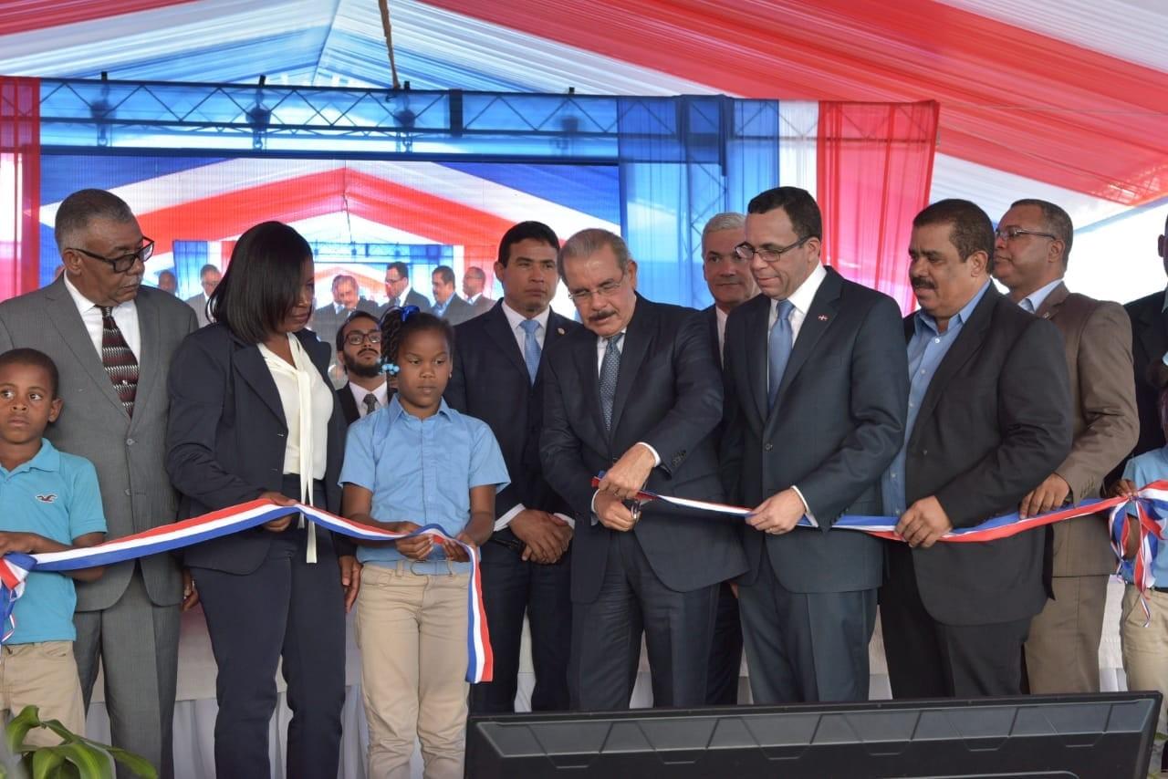 imagen Presidente Danilo Medina de pie cortand cinta junto a Ministros Andrés Navarro, Gonzalo Castillo, Senador Adriano Sánchez Roa y demás autoridades educativas de Elías Piña.