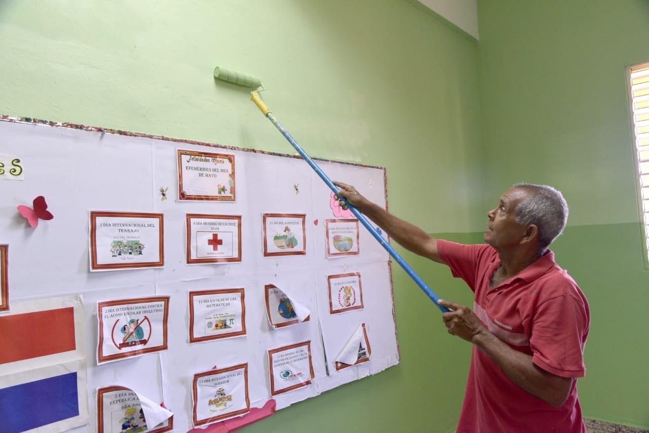 imagen Miembro de mantenimiento escolar pintando aula de centro educativo