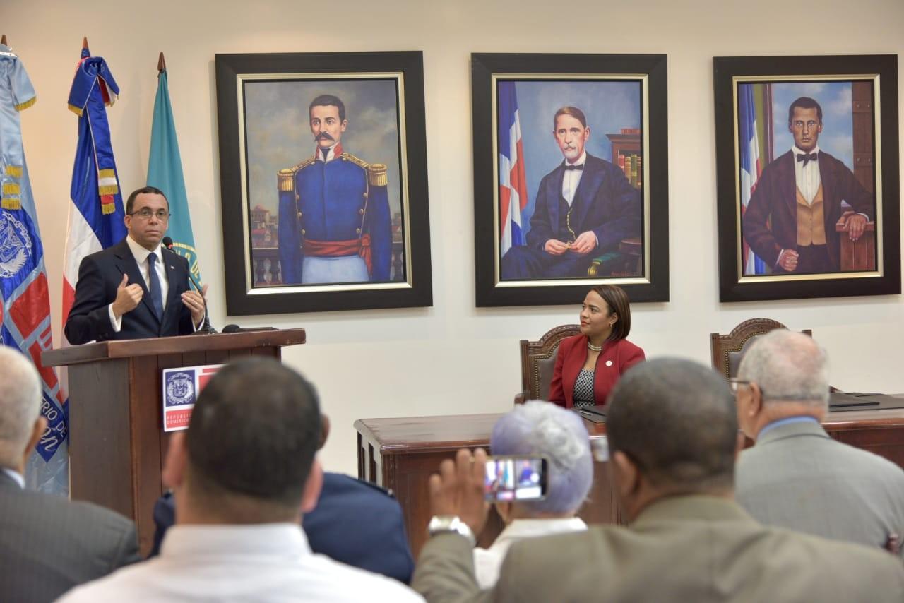 imagen Ministro Andrés Navarro hablando de pie desde podium se dirige a miembros del Círculo de Locutores que están sentados en sillas frente a el.
