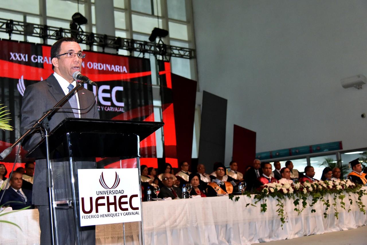 imagen Ministro Andrés Navarro de pie en podium dirigiendo discurso a cientos de profesionaes enXXXI Graduación Ordinaria de la Universidad Federico Henríquez y Carvajal (UFHEC).
