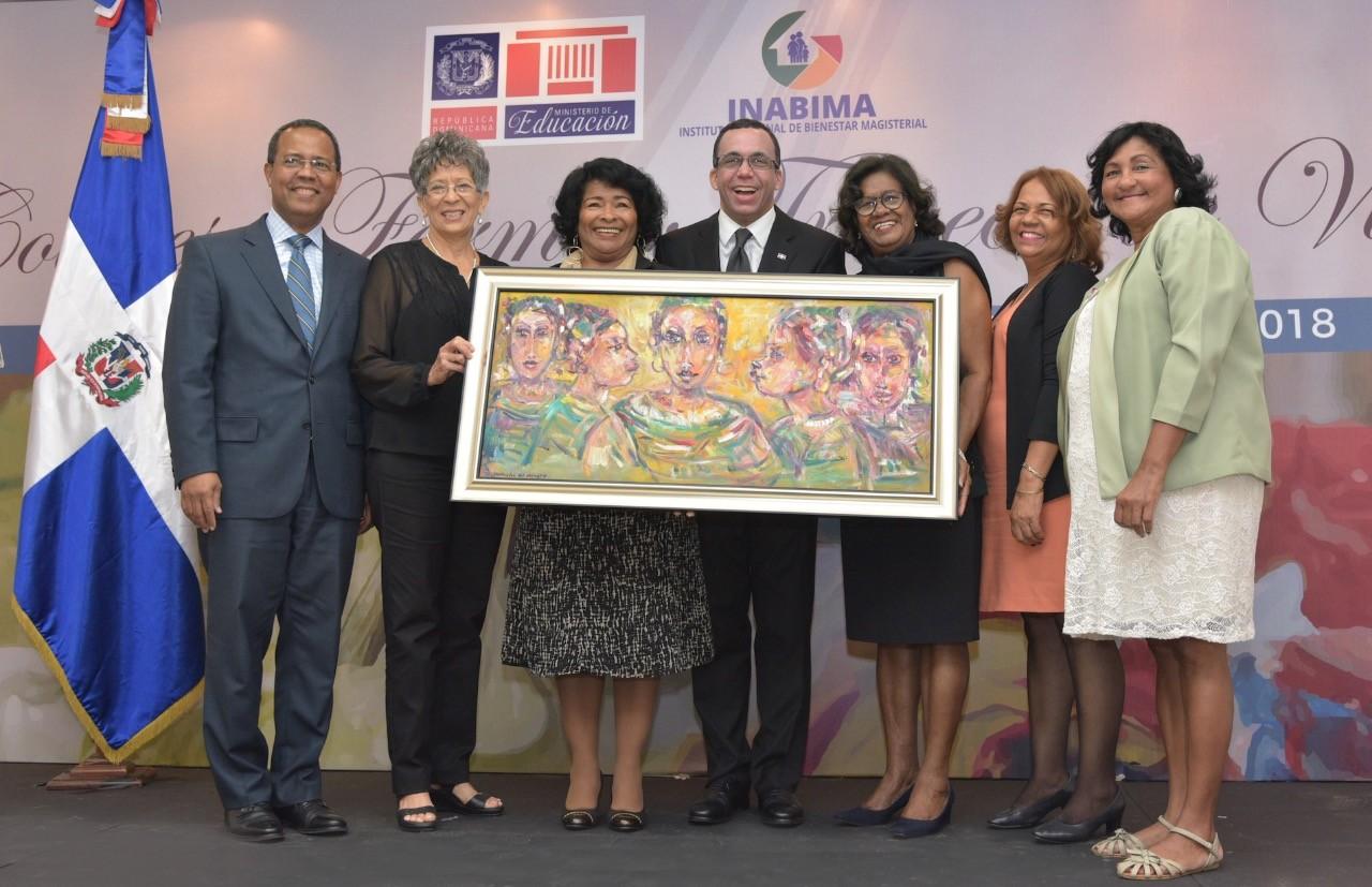 imagen MInistro Andrés Navarro de pie sosteniendo pintura junto a Yuri Rodríguez Director del INABIMA y maestras jubiladas