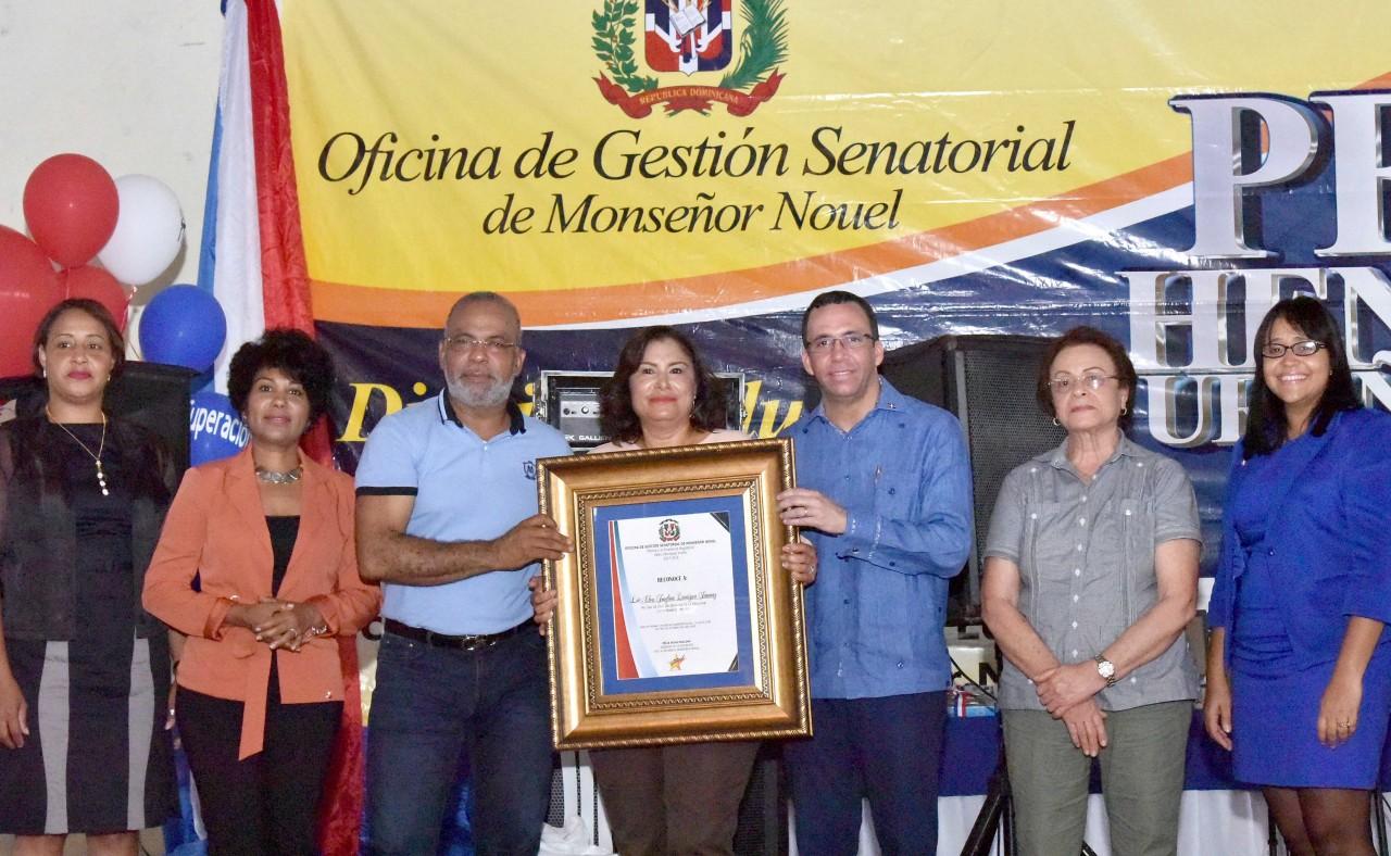 imagen Ministro Andrés Navarro desde tarima junto a Senador Felix Nova entregando reconocimientos a estudiantes y docentes de Monseñor Nouel