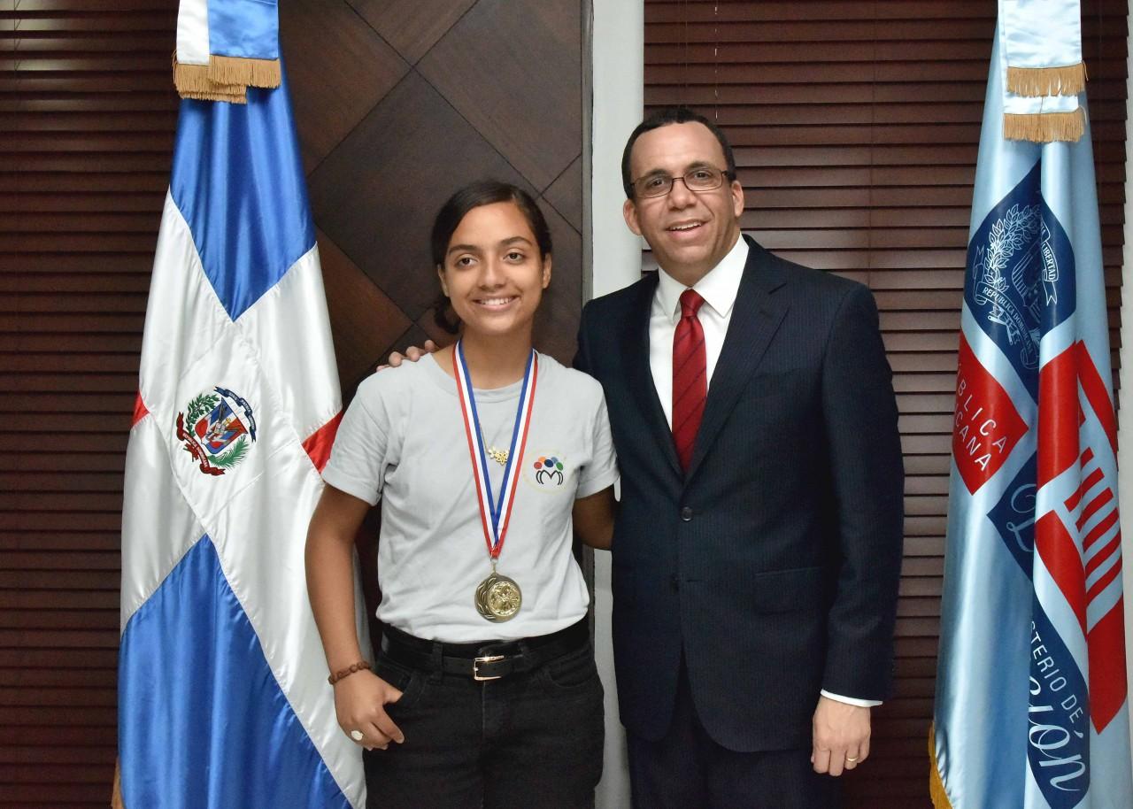 imagen Ministro Andrés Navarro de pie junto a estudiante galardonada en Olimpíadas de Matemática