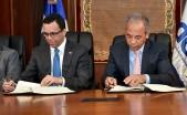 imagen Ministro Andres Navarro y Ruben Bichara sentados firmando acuerdo de cogestion