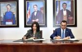imagen Ministro Andrés Navarro y Directora de INTRANT, Claudia Franchesca De Los Santos sentados firmando acuerdo interinstitucional