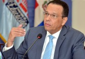 imagen Ministro de educación sentado frente a micrófono durante rueda de prensa.