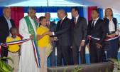 imagen Presidente Danilo Medina de pie cortando cinta junto a Ministro Antonio Peña Mirabal y demás autoridades educativas en acto de entrega de nuevas aulas para Partido en Dajabón