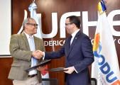 imagen Ministro Andés Navarro de pie junto a presidente del CODUE estrechandose las manos luego de firma de convenio