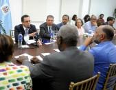 imagen Ministro Andrés Navarro sentado en la mesa junto a integrantes de la ADP, entre otros representantes de distintas áreas. Frente al Ministro, el señorEduardo Hidalgo.