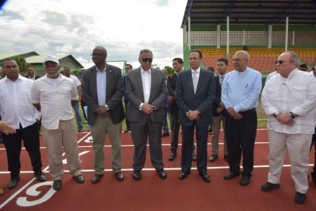 imagen Ministro Peña Mirabal, junto al presidente del Comité Olímpico Dominicano, Luisín Mejía Oviedo,el senador por Monte Plata, Charles Mariotti, autoriades e integrantes de lacomunidad de Bayaguana, mientras caminan sobre moderna pista de atletismo.