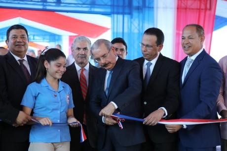 imagen Presidente Danilo Medina de pie cortando cinta junto a Ministro Antonio Peña Mirabal y demás autoridades educativas en acto inaugural