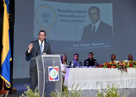 imagen Ministro Andrés Navarro de pie en podium exponiendo discurso al lado de mesa principal en posgrado de la Universidad Católica Nordestana