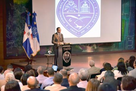 imagen Ministro Andrés Navarro de pie desde podium en auditorio en la UASD se dirige a cientos de personas