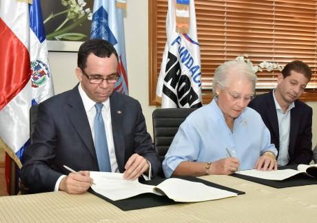 imagen Ministro Andrés Navarro y Margarita Bonetti sentados firmando acuerdo insterintitucional
