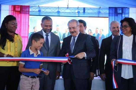 imagen Presidente Danilo Medina de pie cortando cinta junto a autoridades educativas en acto de entrega de dos centros educativos y dos estancias infantiles en Boca Chica y Santo Domingo Este