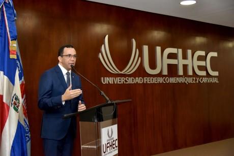 imagen Ministro Andrés Navarro de pie en podium dirigiendo discurso a personas en auditorium de la universidad Federico Henríquez y Carvajal