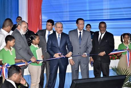 imagen Presidente Danilo Medina y ministro Antonio Peña Mirabal de pie junto a autoridades educativas cortando cinta de acto inaugural