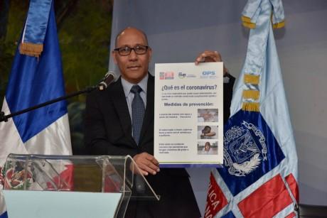 imagen Foto frontal del director de gabiete del MINERD, Henry Santos, sostiene material informativo y didactico sobre el coronavirus.