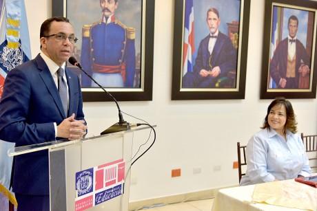 imagen Ministro Andrés Navarro de pie desde podium al lado de Directora General de Compras y Contrataciones quien está sentada en mesa principal dejando aperturado nuevo taller institucional