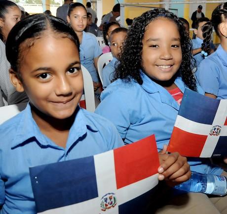 imagen Estudiantes sosteniendo bandera de la República Dominicana durante inauguración de centros educativos en Santiago