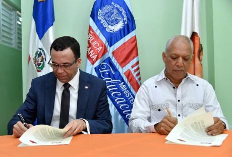 imagen Ministro Andrés Navarro y director de INDARTE sentados firmando acuerdo de cooperación para promover el arte en las escuelas de Capotillo