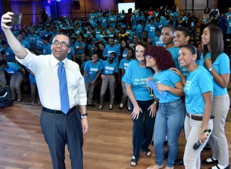 imagen Ministro Andrés Navarro de pie en tarima junto a estudiantes tomandose una selfie