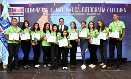 imagen Ministro Andrés Navarro de pie junto a estudiantes galardonados de las olimpíadas de Matemática, Ortografía y Lectura