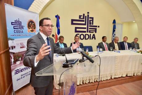 imagen Ministro de Educación Andrés Navarro de pie en podium dirigiendo conferencia magistral en el Colegio Dominicano de Ingenieros, Arquitectos y Agrimensores.